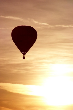 Hot air balloon floating high in the evening sky, England