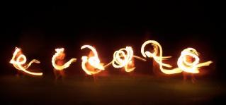 Dancers illuminated by flaming batons at a Hawaiian luau.
